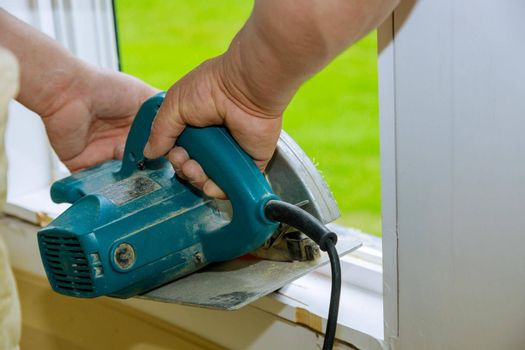 Cutting wooden trim board on with hand circular saw works on remodeling home