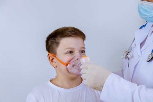 Doctor help child patient at inhaling through oxygen mask