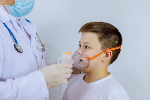 Hospital doctor helps a child patient breathe through on oxygen mask.