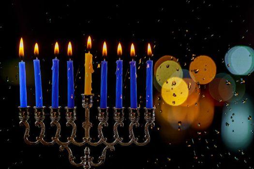 Jewish Religion holiday symbol for Hanukkah in hanukkiah Menorah with burned candles with bokeh