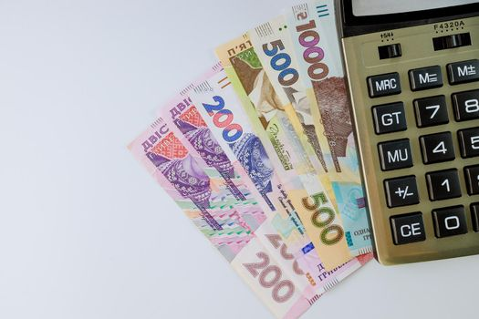 Financial accounting calculate the calculator on the Ukrainian money hryvnia banknotes with on white background