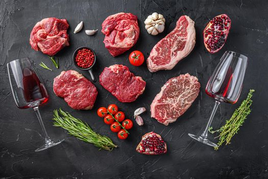 Set of various beef steak cuts, chuck roll, rump andtop blade steak with herbs, seasoning and red wine glass on black table, top view.