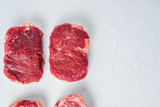Raw rump steak. Organic beef. White textured background. Top view with space for text.