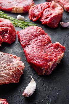 Rump beef steak cuts, with herbs, seasoning on black table, side view.