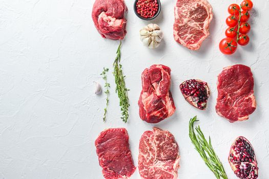 Beef cuts Chuck eye roll, top blade, rump steakwith herbs and pomegranate. Organic meat. White textured background. Top view with space for text.