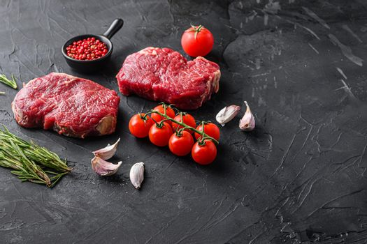 Raw rump steaks from organic beef meat cuts with rosemary, garlic and spices over black textured background, top view space for text.