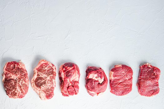 Raw set of alternative beef cuts Chuck eye roll, top blade, rump steak. Organic meat. White textured background.Top view with space for text.