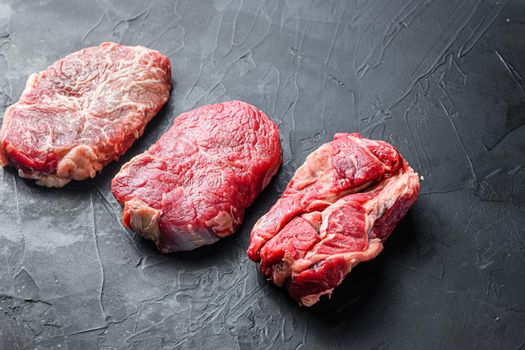 Set of organic alternative cuts beef steaks, top blade, rump and chuck roll, on black textured background, side view with space for text.