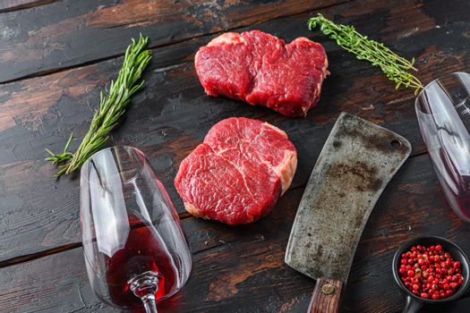 Raw rump steaks with american butcher cleaver and two glass of red wine over dark old wooden background, side view.