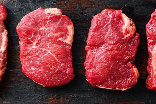 Set of raw beef rump steaks on old wooden dark planks top view