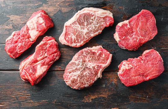 Variety of fresh Black Angus Prime raw beef steakes on old rustic dark wooden background, top view.