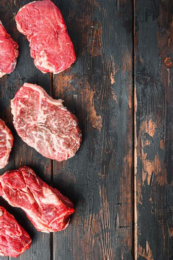 Variety of fresh Black Angus Prime raw beef steakes on old rustic dark wooden background, top view with space for text.