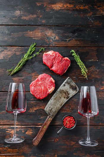 Raw rump steaks with american butcher cleaver and two glass of red wine over dark old wooden background, top view space for text.