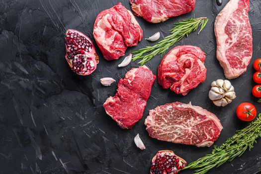 Alternative raw beef steak cuts with top blade, chuck roll and rump steak, with herbs and pomegranate top view, space for text.