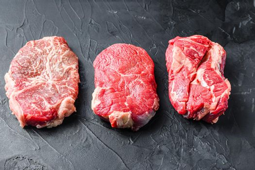 Set of raw alternative cuts beef steaks, top blade, rump and chuck roll, on black textured background, side view.