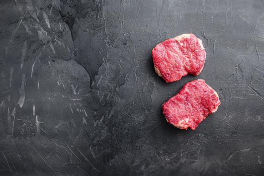 Raw rump steaks over black background, top view with space for text.