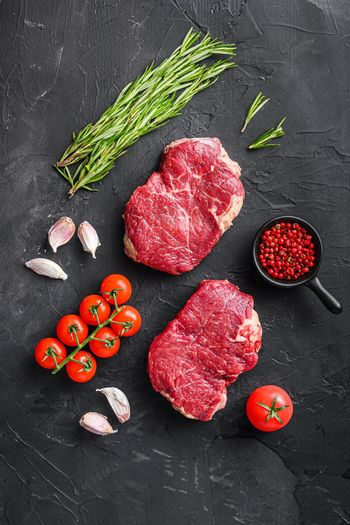 Raw rump steaks from organic beef meat cuts with rosemary, garlic and spices over black textured background, top view.