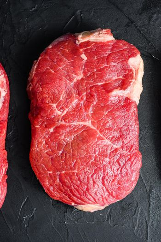Raw rump beef steak cut, on black textured background, top view.