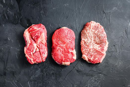 Set of raw alternative cuts beef steaks, top blade, rump and chuck roll, on black textured background, top view.