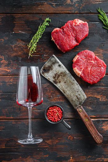 Raw rump steaks with american butcher cleaver and two glass of red wine over dark old wooden background, top view.