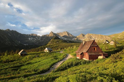 Cottage in a valley surrounded by the Carpathian Mountains.