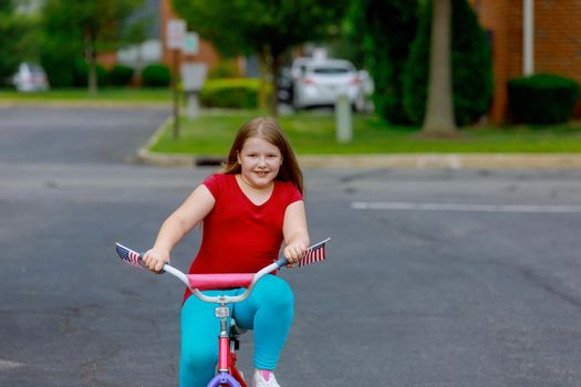 Smiling little girl in summer clothes riding bicycle at the park on a city