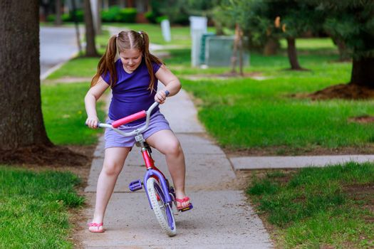 Little girl is biking the in the park on a city