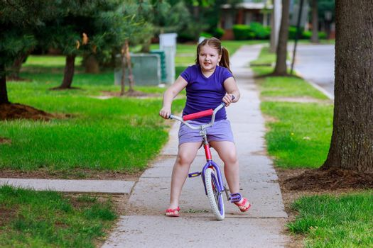 Beautiful little girl smiling is riding the bicycle in the park a city