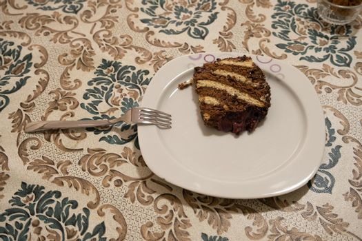 It depicts a slice of chocolate cake in the kitchen