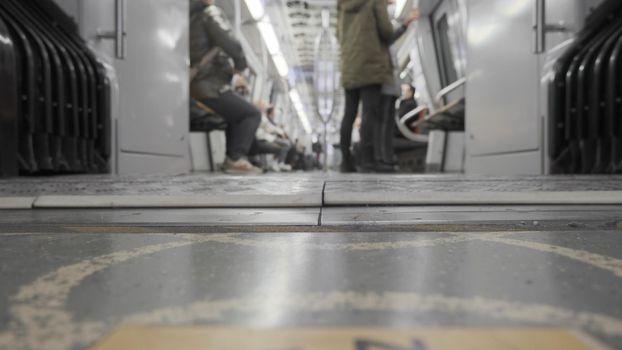 It depicts some metro passengers standing in front of subway door