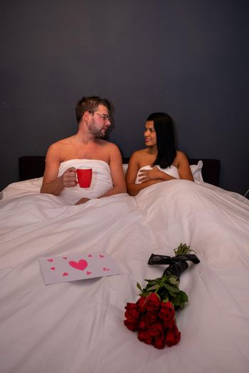 Happy valentine's couple, mid-age Asian woman with European man with red roses and a love letter on Valentine day 14 February, couple in bed with red roses and valentine card