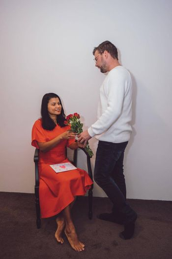 Happy valentine's couple, mid-age Asian woman with European man with red roses and a love letter on Valentine day 14 February