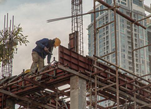 Construction Worker Welding soldering metal girders and Sparks.