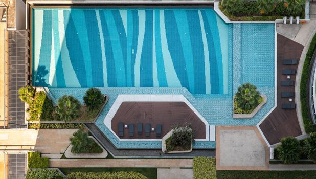 Bangkok, Thailand - 02 Jan 2020 : Top down aerial view of outdoor swimming Pool surrounding palms and green garden in the beautiful condominium. Modern landscape architecture with swimming pool.