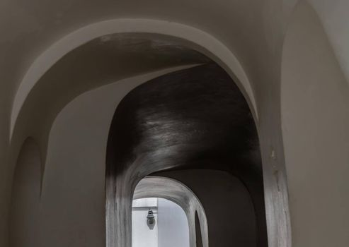 Corridor Under the Ancient building with cement wall on both sides leading into exit. Selective focus.