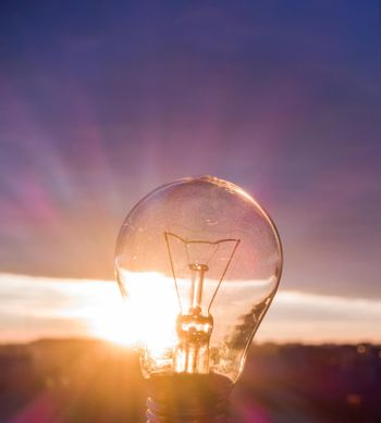 A lamp in the sun. Pure light energy. A beautiful sunset through an incandescent lamp.
