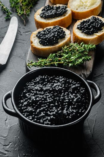 Sandwiches with black caviar, on black background