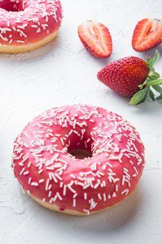 Bitten strawberry donut, on white background