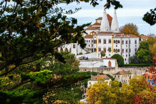 Sintra, Portugal - October 28, 2020: Architectural detail of the National Palace of Sintra, also called the Royal Palace with its 2 chimneys of 33 meters behind trees on a winter day