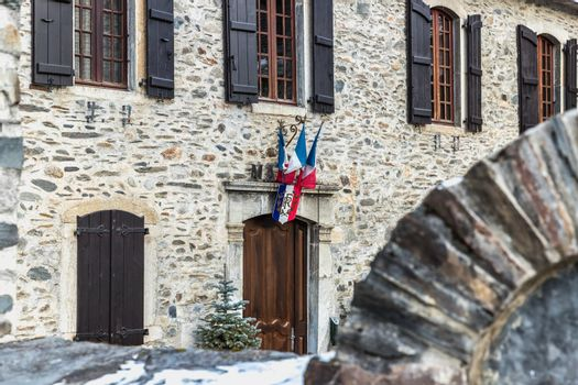Saint Lary Soulan, France - December 26, 2020: architectural detail of the town hall in the historic city center where tourists walk on a winter evening