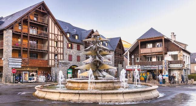 Saint Lary Soulan, France - December 26, 2020: fountain in the city center frozen by the cold on a winter day
