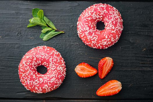Bitten strawberry donut, on black wooden table background, top view flat lay