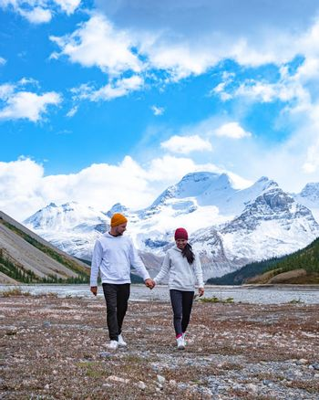 couple mid age men and woman hiking in the Canadian Rockies near Alberta Banff national park with snowy mountains
