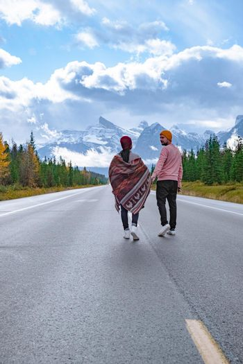 couple walking over The road 93 beautiful Icefield Parkway in Autumn Jasper National park,Canada