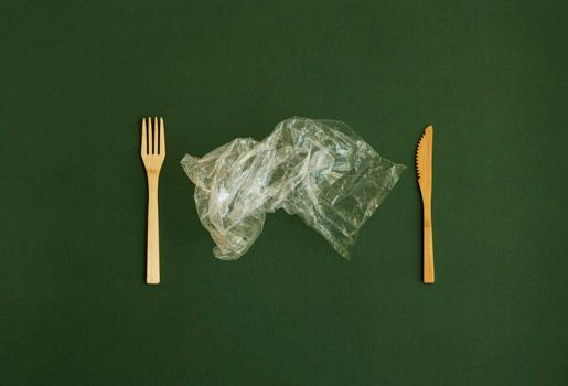 Crumpled plastic polyethylene bag with a bamboo fork and knife on a green background. Contamination of the planet. Clear plastic bag. Zero waste concept.