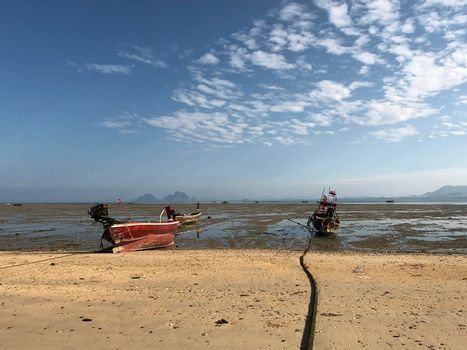 Long-tail boats during low tide in Koh Mook