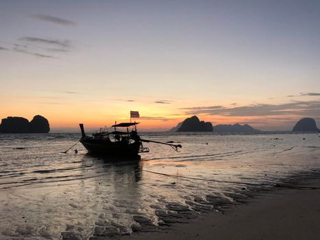 Long-tail boat during sunrise and low tide