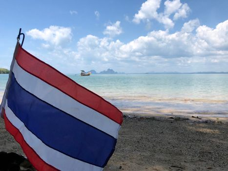 Thai flag with a Long-tail boat in the background