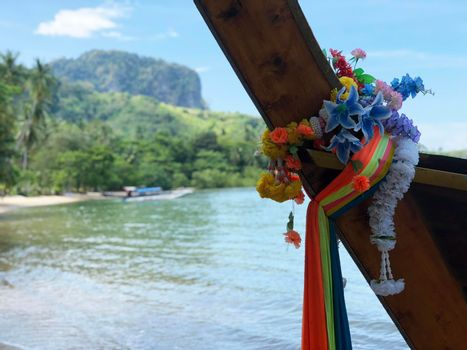 Colorful clothes tied to bow of long-tail boat