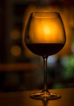 glass of red wine in dark cozy bar interior